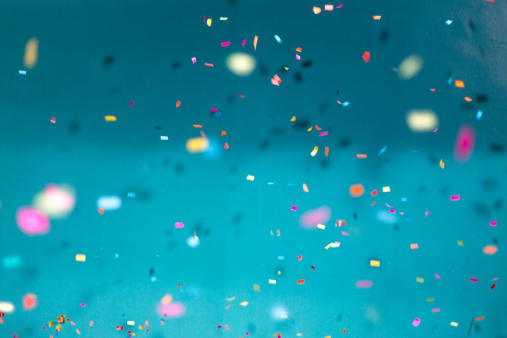 Confetti, tossed into the air, contrasted against a bright blue background.