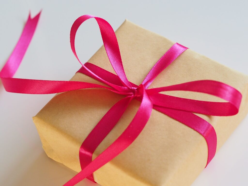 A square gift, wrapped in brown paper with a bright pink ribbon bow.
